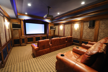 home theater with custom cabinetry and theater seating in large media room